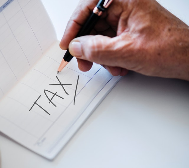 A pad with tax written on it with a hand holding a pen above it.